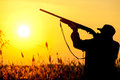 Hunter rifle silhouetted in beautiful sunset summer Royalty Free Stock Image