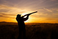 Hunter shooting in sunset a female bird silhoutted against a dramatic with shotgun shouldered position Stock Photo