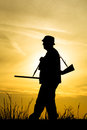 Hunter with shotgun in sunset on the field Royalty Free Stock Photography