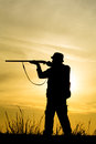 Hunter with shotgun in sunset on the field Royalty Free Stock Image