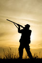 Hunter with shotgun in sunset on the field Stock Photo