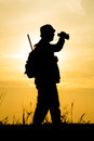 Hunter with shotgun in sunset on the field Royalty Free Stock Photo
