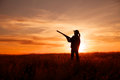 Hunter in sunset a female bird silhoutted against a dramatic with shotgun Stock Images