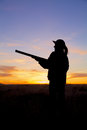 Hunter in sunset a female bird silhoutted against a dramatic with shotgun Stock Photos