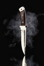 Hunting knife with smoke on a black background Royalty Free Stock Photo