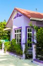 Purple house with white wooden windows under a red roof against a blue sky. Royalty Free Stock Photo