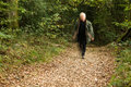 Hurry white or silver haired senior citizen in a along a woodland path Royalty Free Stock Photography