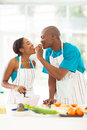 Husband feeding wife loving african a piece of tomato while cooking Stock Image