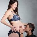 Husband kissing the stomach of his pregnant wife Royalty Free Stock Photos