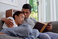 Husband read wife sleep young kiss sleeping forehead in arms on sofa couch in home living room Stock Images