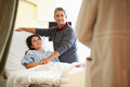 Husband visiting wife in hospital and talking to doctor happy who is recovering Royalty Free Stock Photos