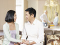 Husband and wife asian couple sitting on couch looking at each other with their senior parents in the background Stock Photography