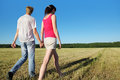 Husband, wife hold walk in field near wood Stock Photos