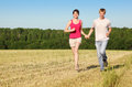 Husband, wife holding hands run in field Royalty Free Stock Images