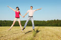 Husband, wife in jump in field Royalty Free Stock Photos