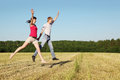Husband, wife jumping in field Stock Image