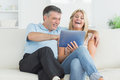 Husband and wife laughing at tablet pc on the sofa Stock Photography