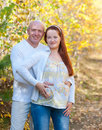 Husband and wife prospective parents happy married couple his pregnant at walk in autumn forest Royalty Free Stock Photography