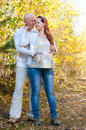 Husband and wife prospective parents happy married couple his pregnant at walk in autumn forest Stock Images