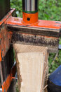 Hydraulic wood splitter closeup view of an ash log being processed with a Royalty Free Stock Images