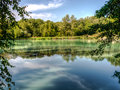 Hydrogen sulfide lake hydrogen sulfide lake landscape with turquoise water in tree branches framing. Royalty Free Stock Photo