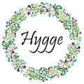 Hygge sign symbolizing Danish Life style surrounded by colorful floral wreath elements in the shape of a circle