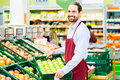 Hypermarket clerk filling up storage racks supermarket apple in fruit department Stock Image
