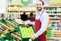 Hypermarket clerk filling up storage racks supermarket apple in fruit department Royalty Free Stock Images