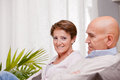 I am a happy realized woman old women and old men together because they love each other in living room on sofa Stock Photo