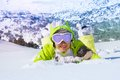 I love all this snow young smiling woman in ski glasses laying in with mountain on background Royalty Free Stock Image