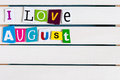I Love August written with color magazine letter clippings on wooden board. Summer vacation concept, empty space for