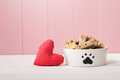 I love my dog concept with a red textile heart alongside a doggy bowl decorated with a paw print and filled with biscuits pink Stock Photo