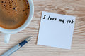 I love my job motivation inscription on peace of paper at workplace near morning coffee cup. With empty space for text