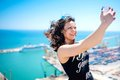 I love selfie portrait of beautiful brunette girl taking photographs of herself selfies on the shore at seaside modern concept Royalty Free Stock Photography