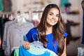 I love shopping wider shot of a happy girl carrying a few dresses before trying them on and smiling Royalty Free Stock Photography