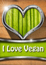 I love vegan metal porthole heart shape with green vegetables interior on wooden wall and written Stock Photography
