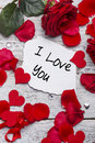 I love you card on wooden board with petals Stock Photo