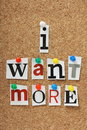 I want more the phrase in cut out magazine letters pinned to a cork notice board Stock Photo