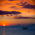 Ibiza sunset es vedra view and fisherboat formentera menorquina from orange sky Stock Photos