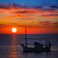 Ibiza sunset view and fisherboat formentera menorquina from orange sky Stock Image