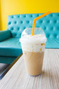 Ice blend caramel coffee with green chair and yellow wall background Royalty Free Stock Images