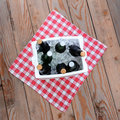 Ice chest full of beer on a table cloth on a wood deck overhead shot styrofoam bottles red and white checked square format Royalty Free Stock Photos