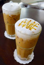 Ice coffee with milk and caramel put on the table Royalty Free Stock Photography