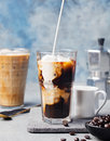 Ice coffee in a tall glass with cream poured over and coffee beans on grey stone background Royalty Free Stock Image
