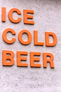 Ice cold beer spelled out in bold orange block letters Royalty Free Stock Photos