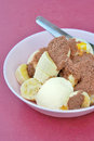 Ice cream with banana scoops of vanilla topping cocoa or chocolate powder Royalty Free Stock Image