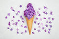 Ice cream of lilac flowers in waffle cone on gray background from above, beautiful floral arrangement, flat lay Royalty Free Stock Photo