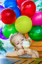 Ice cream little girl eating an with balloons at the background Royalty Free Stock Images
