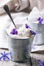 Ice cream with sugared violets served in little metal pail on old wooden table see series Stock Photos