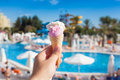 Ice cream and summer background man holding cone in front of a swimming pool Stock Images